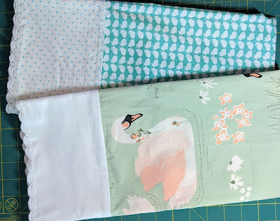 A blue print with bunnies and a pale green print with pink and white swans are sewn into pillowcases with white cuffs and white crochet edging