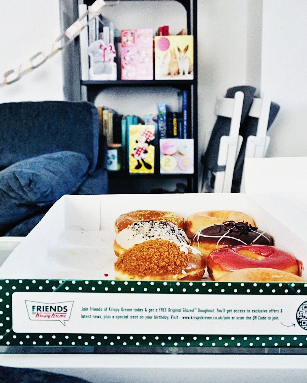 Krispy Kreme donut tray with bookshelf and birthday cards in the background.