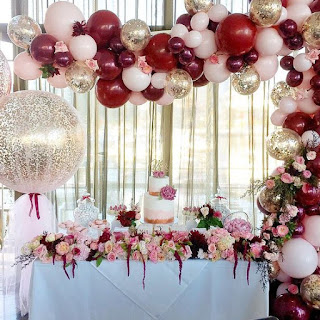 Burgundy, blush, gold confetti balloons, and flowers balloon arch