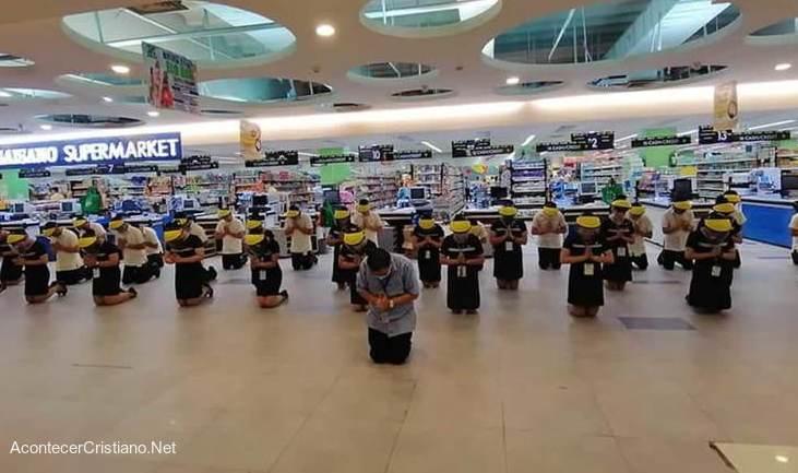 Trabajadores de supemercado orando de rodillas