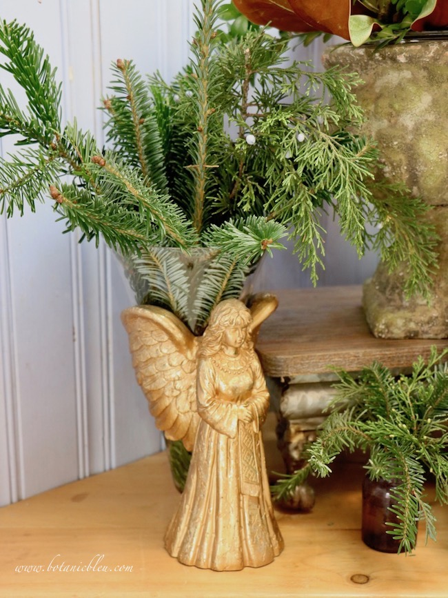 An angel flower vase holding fresh evergreens will be replaced with a simpler mercury vase to transition from Christmas to Winter decor