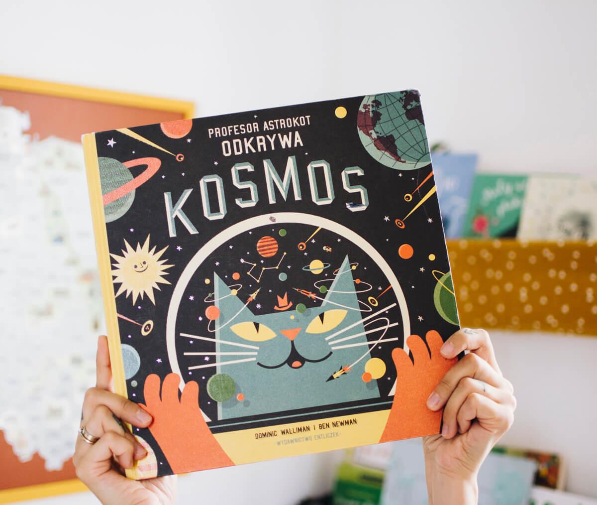 Dłonie trzymające książkę dla dzieci Profesor Astrokot odkrywa kosmos