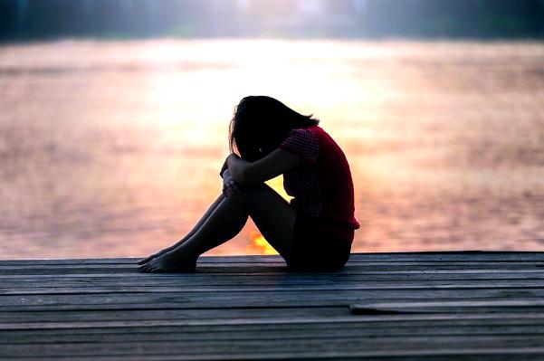 A imagem mostra uma garota sentada em um píer com a cabeça baixa na beira do lago.