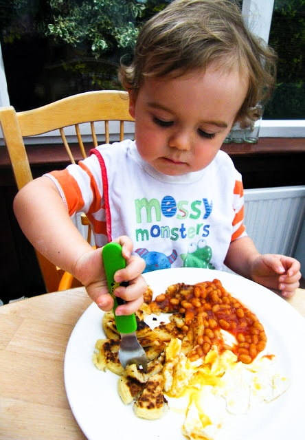 toddler eating tattie scones  with baked beans and eggs