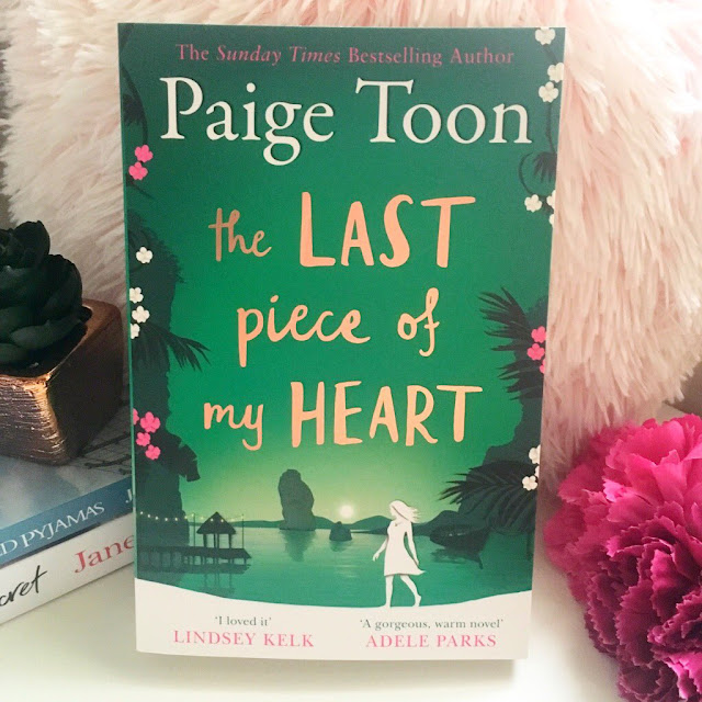 Pink fluffy cushion in the background, book 'The Last Piece Of My Heart by Paige Toon' propped up against it. 2 flowers laid down to the right hand side and a gold ornament to the left of it]