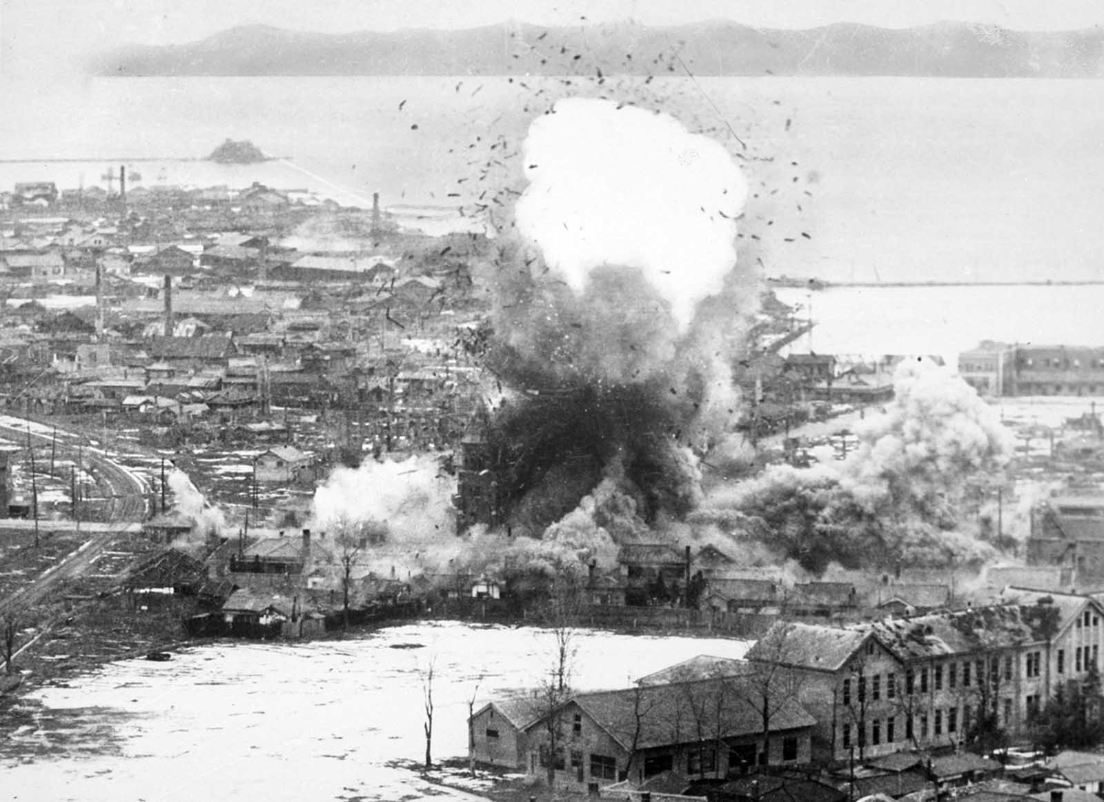 Supply warehouses and dock facilities at this east coast port explode after para-demolition bombs were dropped from the Fifth Air Force's B-26 Invader light bombers. Wonsan, North Korea, 1951.