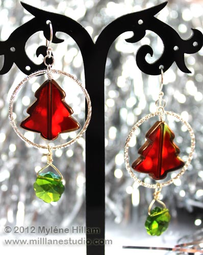 Red Christmas tree suspended inside a silver hoop with a dangling green marguerite bead below it.