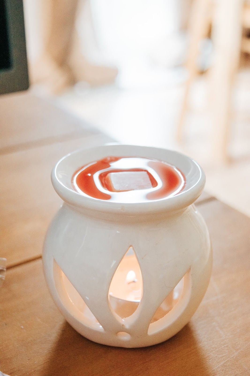 A white wax melt burner with a red and orange wax melt melting on top