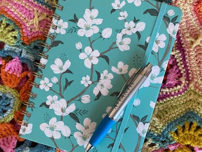 Journal with flowers and pen on crochet blanket
