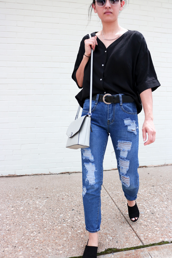Ripped blue jeans, black mules, sandals, vintage belt, gray bag, black shirt