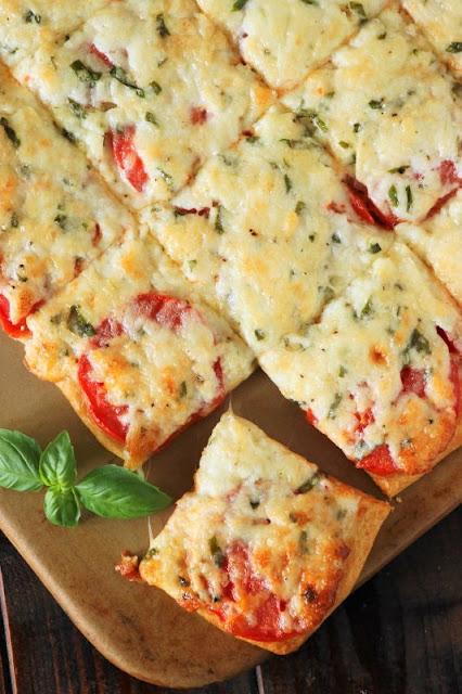 Fresh tomatoes and basil slathered with melty cheese, and layered on a crescent roll crust ~ the perfect versatile savory little treat. Enjoy Crescent Roll Tomato-Basil Squares for a party, lunch, brunch, or even as a tasty afternoon snack.