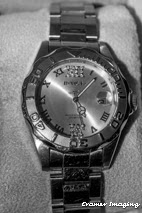 Cramer Imaging's professional quality product photograph of a silver wrist watch in black and white in a box