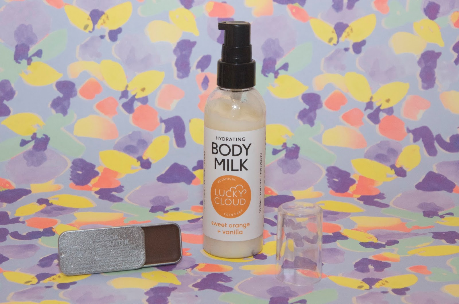 Lotion, lip balm and floral background