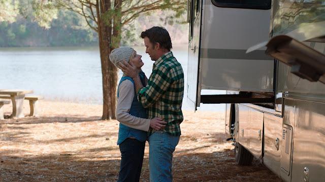 Na imagem, o trailer à direita, um pouco da paisagem à esquerda e o estranho casal Paul e Wendy meio que se reconfortando, quase com sorrisos nos lábios, com ele segurando com as mãos ambas as faces do rosto dela, e as mãos dela na cintura dele.