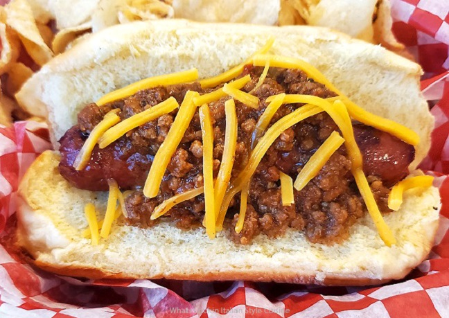 this is a chili cheese hot dog with salt and vinegar chips on a red and white check