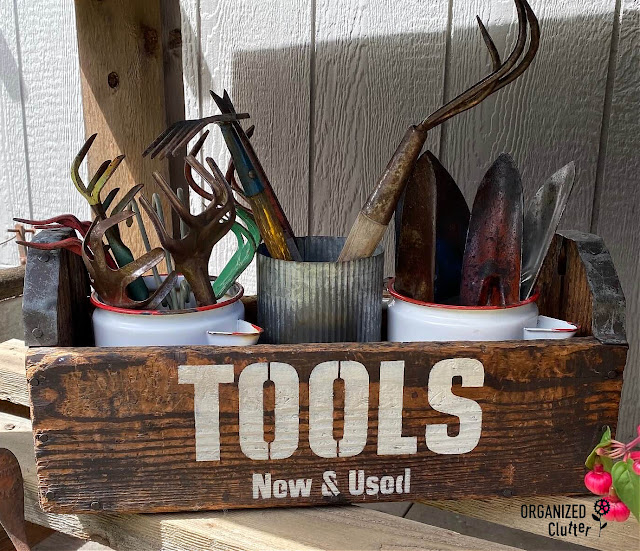 Photo of a vintage toolbox stenciled with a garden tools stencil and filled with garden tools