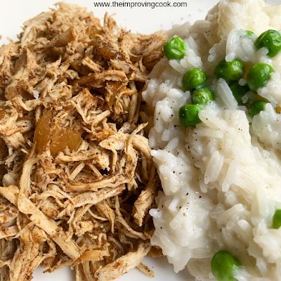 Plate of shredded jerk chicken with coconut rice and peas