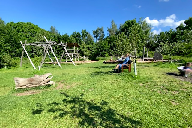 A view from the entrance of Hanningfield reservoir playground showing 2 large climbing frames with slides, swings and more