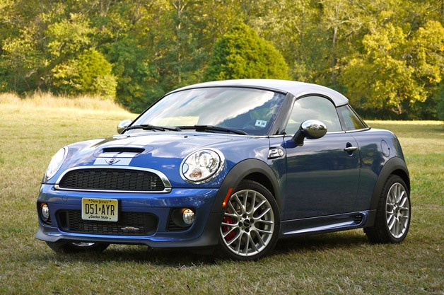 Front 3/4 view of blue 2012 Mini John Cooper Works Cooper Coupe with silver top parked in country setting