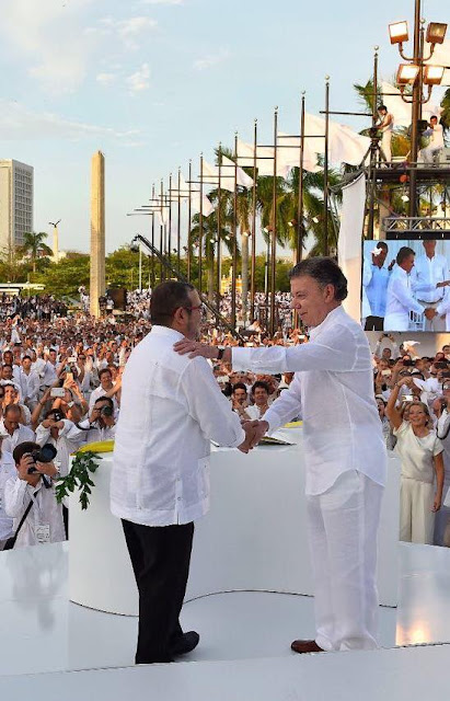 Colombian President Juan Manuel Santos shakes hands with Farc leader Timochenko before signing the peace deal in the city of Cartagena ...