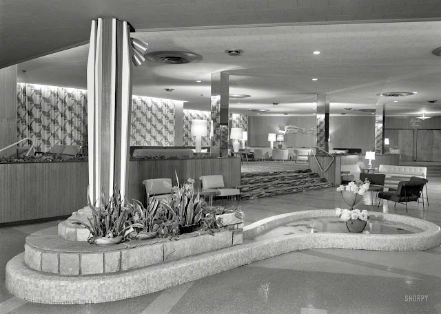 a 1957 hotel lobby with island and pond, and rock stairs