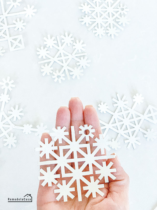 Metal snowflakes on white background and one on hand
