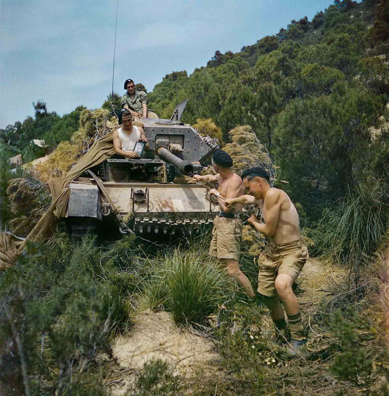 A crew from the 16th/5th Lancers, 6th Armoured Division, clean the gun barrel of their Crusader tank at El Aroussa in Tunisia. 1943.