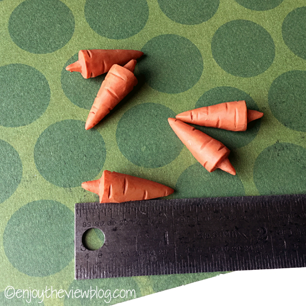 tiny carrot noses lying next to a ruler to show size