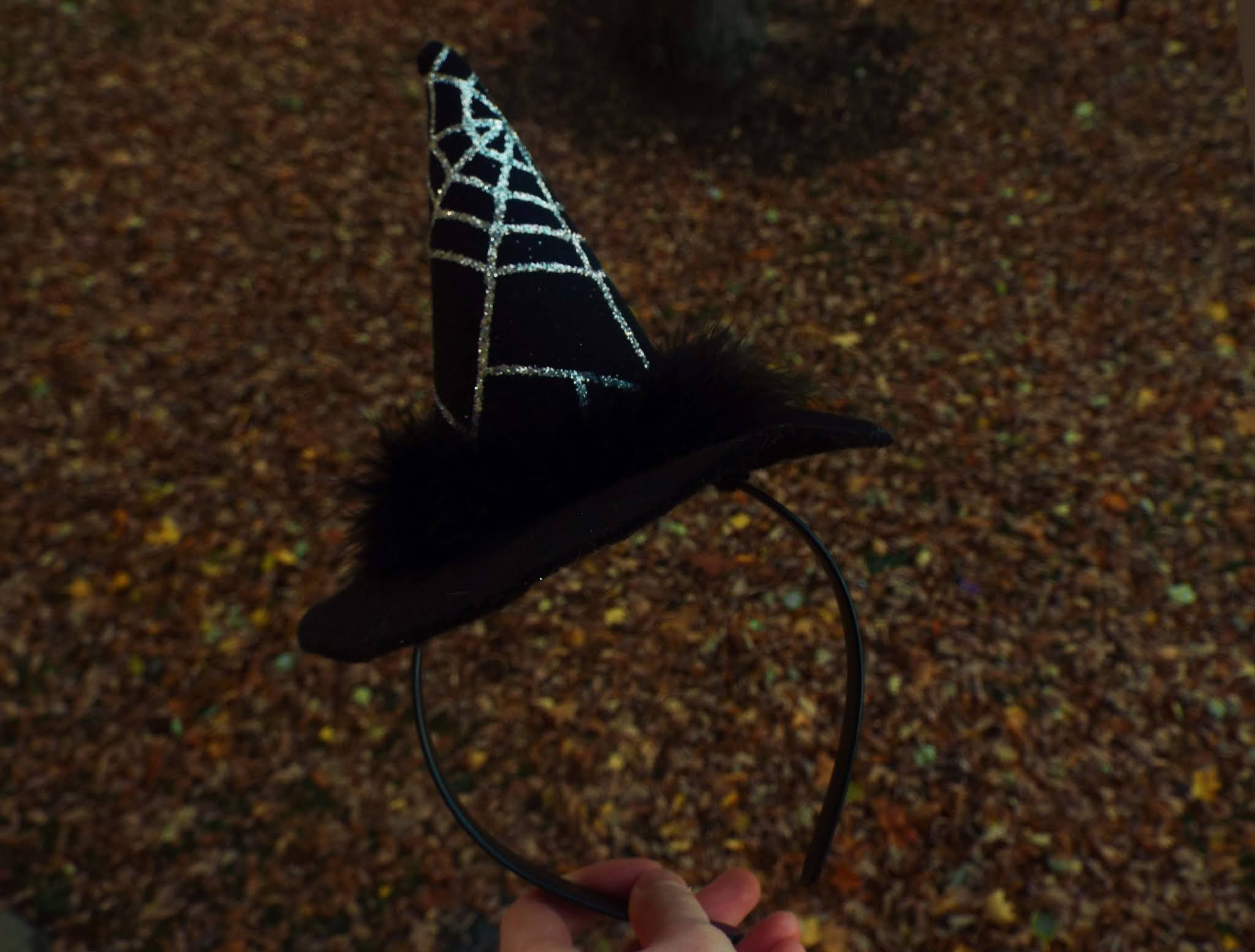 Witches hat held out in Autumnal, golden, leafy backdrop, symbolising my Hallotober Tag.