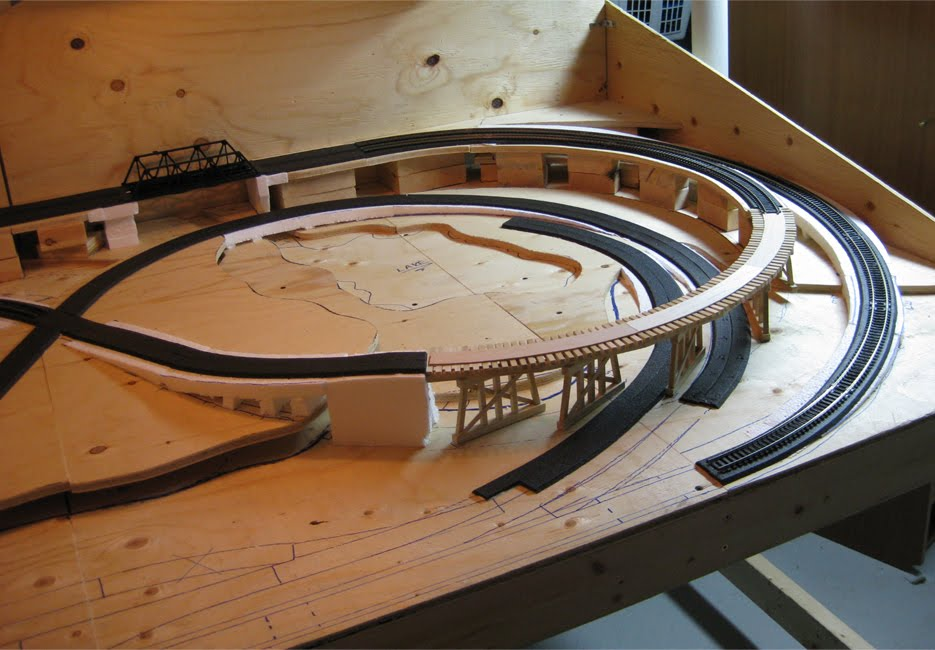 Benchwork showing the almost completed foam roadbed and wooden train trestle