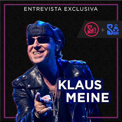 """Na imagem, sobre um fundo preto, há uma foto de Klaus Meine, usando óculos escuros e apontando o dedo para a câmera. No topo, em letras de cor branca, está escrito: """"Entrevista Exclusiva"""", em cima da foto do Klaus, está o nome dele """"Klaus Meine"""" com um contorno azulado. Do lado direito da imagem, estão os logos da Scorpions News e do Scorpions Brazil."""