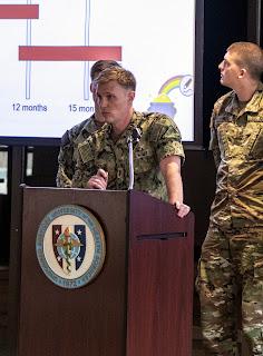 Three students stand at a podium