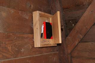 In einem Holzkasten befindet sich eine schwart-rote Kladde und ein Kugelschreiber