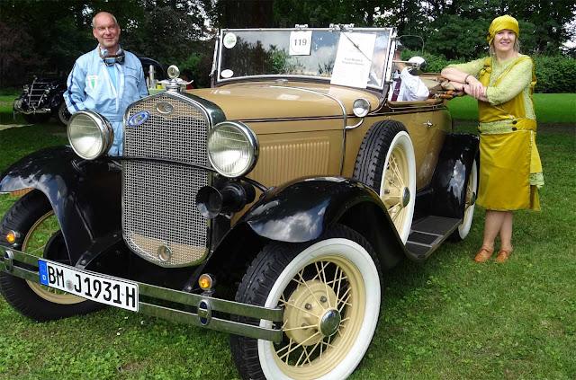 Historischer Ford mit Mann in Mechaniker Uniform und Dame mit grünem Charleston Kleid