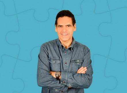 Foto do professor Eugênio Cunha que está sorrindo e com os braços cruzados com o fundo azul.