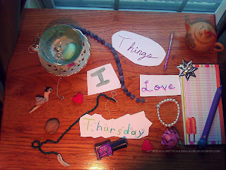 A collection of items arranged as a collage on a small wooden table.  Words written on cut out white paper reads: Things I Love Thursday.  Assorted items in collage include: A mint and white teacup and saucer filled with crystal stones, a quartz pendulum, and a plastic macaroon.  A walnut, two (2) red hearts, a snail wearing a black beret, two (2) strands of stone beads (purple fluorite and green aventurine), a bottle of purple nail polish, a pink rose, a silver colored seven pointed star candle holder, a small tan tea pot, a note pad in summery colors with the image of a popsicle on it, and a decorative pen.
