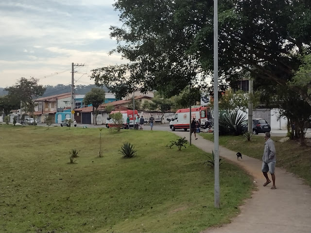 Paisagem de praça, com área de gramado e árvores do lado direito da imagem, com duas ambulâncias do Samu paradas no centro da imagem e algumas pessoas caminhando em volta.
