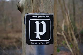 Ein schwarzes Blechschild mit einem verschnörkelten, weißen P darauf. Das P ist von einem Viereck umrandet und das Blechschild auf einem Holzpfosten befestigt