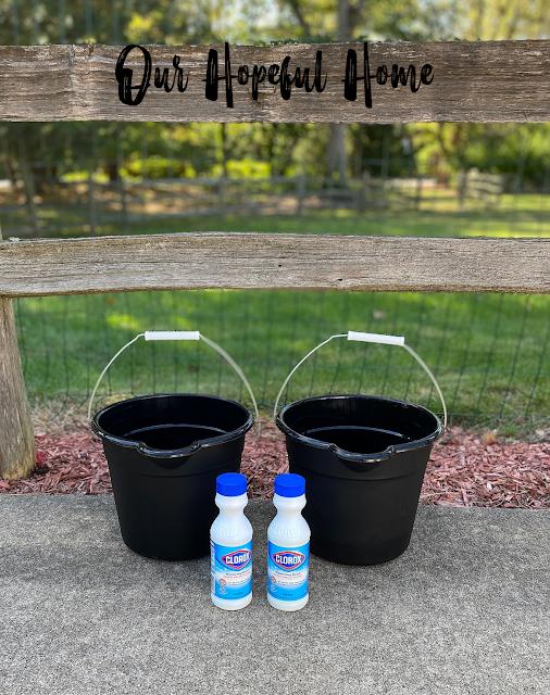 two black buckets two bottles Clorox Bleach in driveway