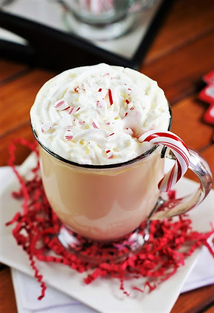 Mug of White Chocolate Peppermint Eggnog Topped with Whipped Cream and Candy Cane Garnish