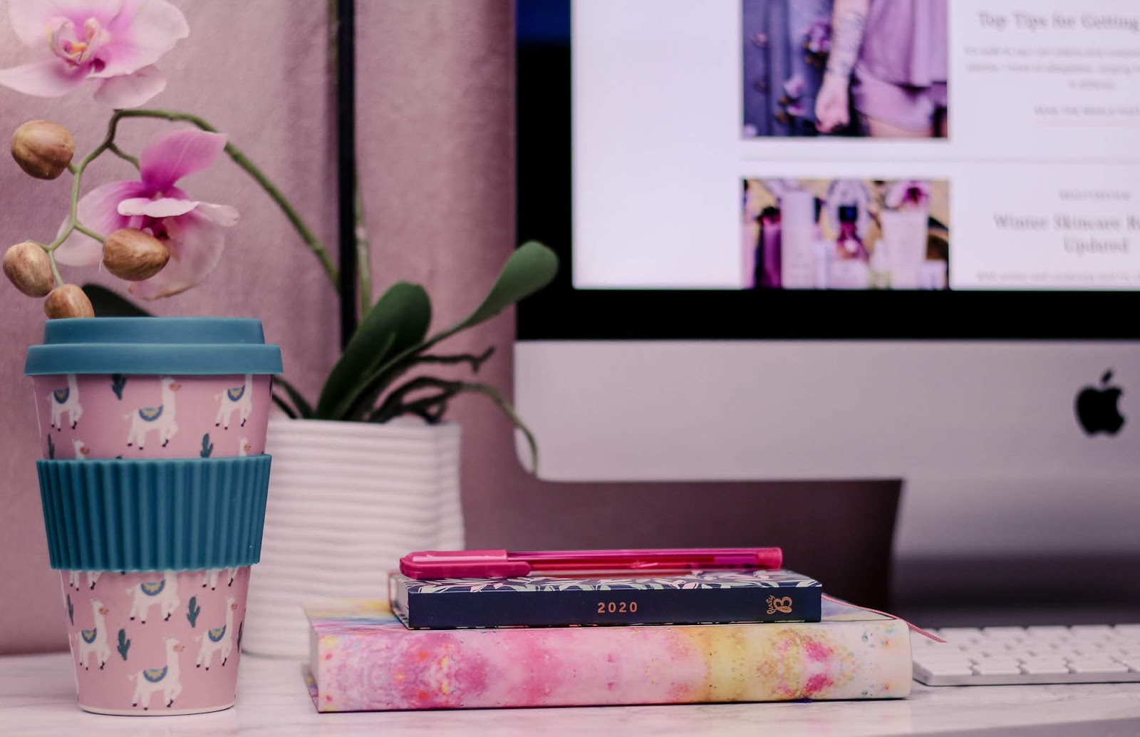 Photo of a pink and blue travel coffee mug, pink notebook, 2020 diary and pink pen sitting on a white marble computer desk with a pink orchid and iMac blurred in the background.
