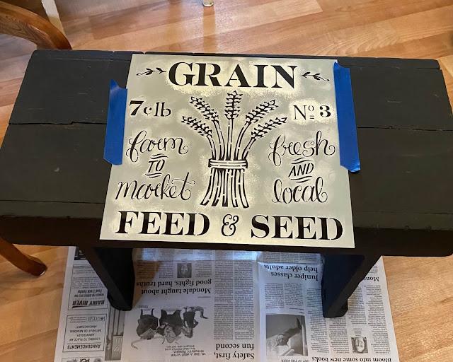 Foto de um estêncil de grãos em um banco preto.