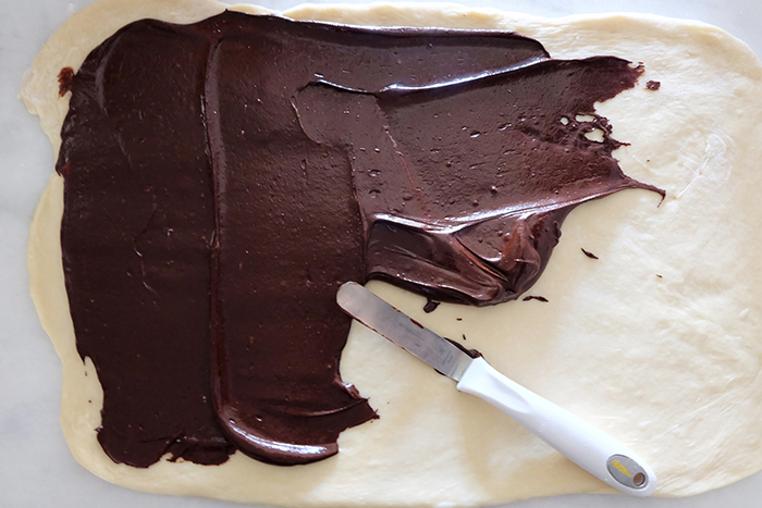 spreading chocolate filling across dough