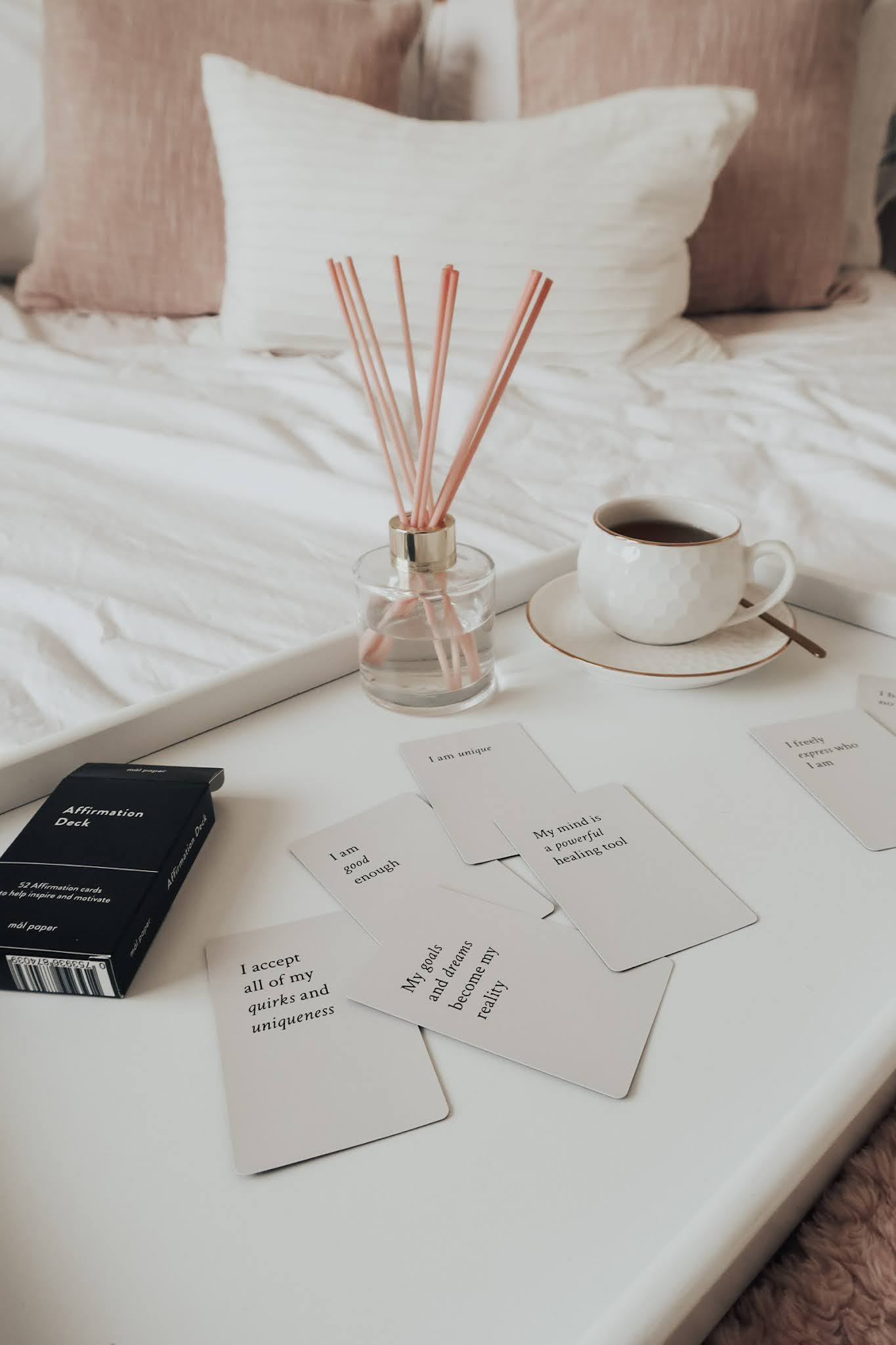 Splayed white affirmation cards on a white tray.
