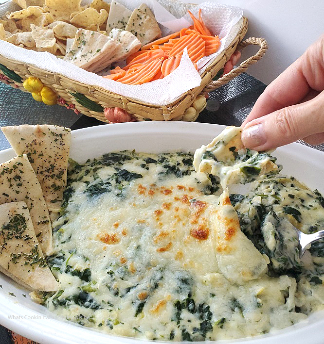 this is a baked artichoke and spinach dip with carrots, chips and pita points for dipping into this baked party dip