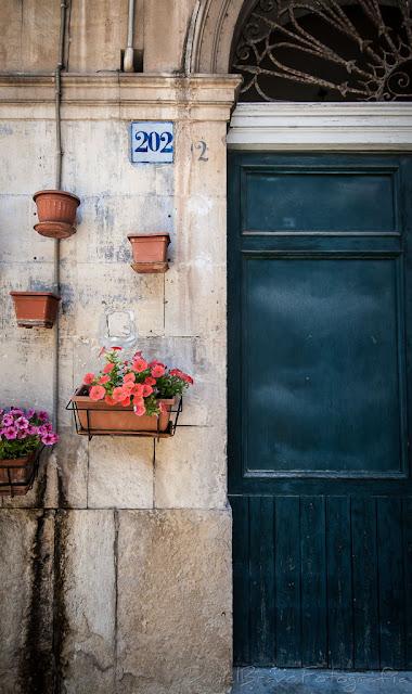 Pared y puerta de un portal decorado con plantas y diferentes macetas, en la ciudad de Ragusa en Sicilia