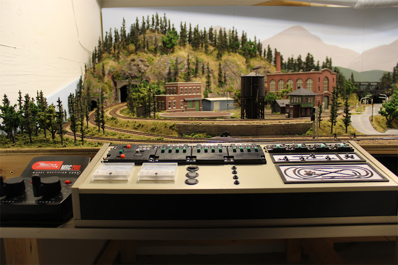 Custom built model railroad control panel with mountain forest and industrial scenery in the background