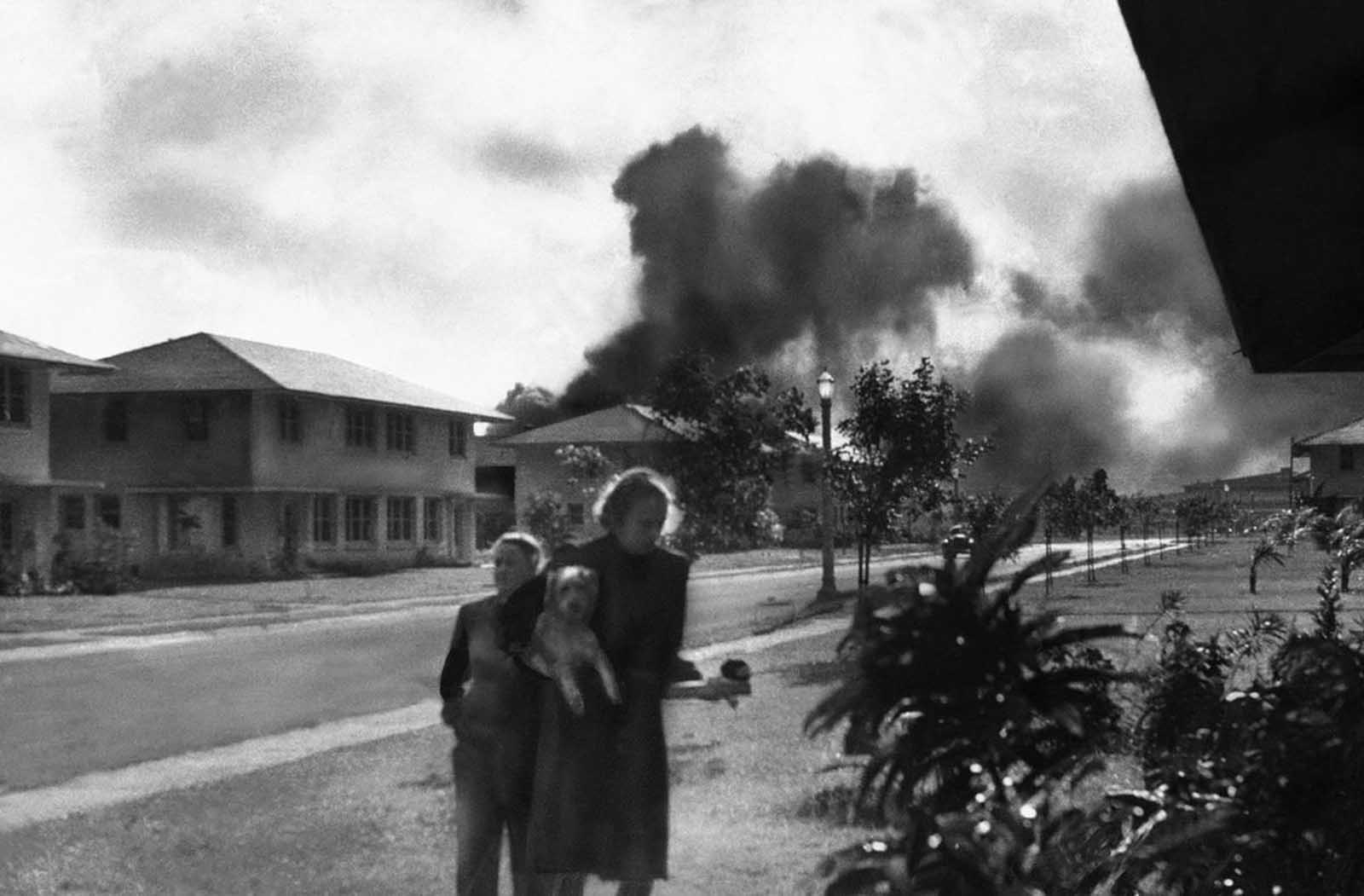 Officers' wives, investigating explosions and seeing a smoke pall in distance on December 7, 1941, heard neighbor Mary Naiden, then an Army hostess who took this picture, exclaim