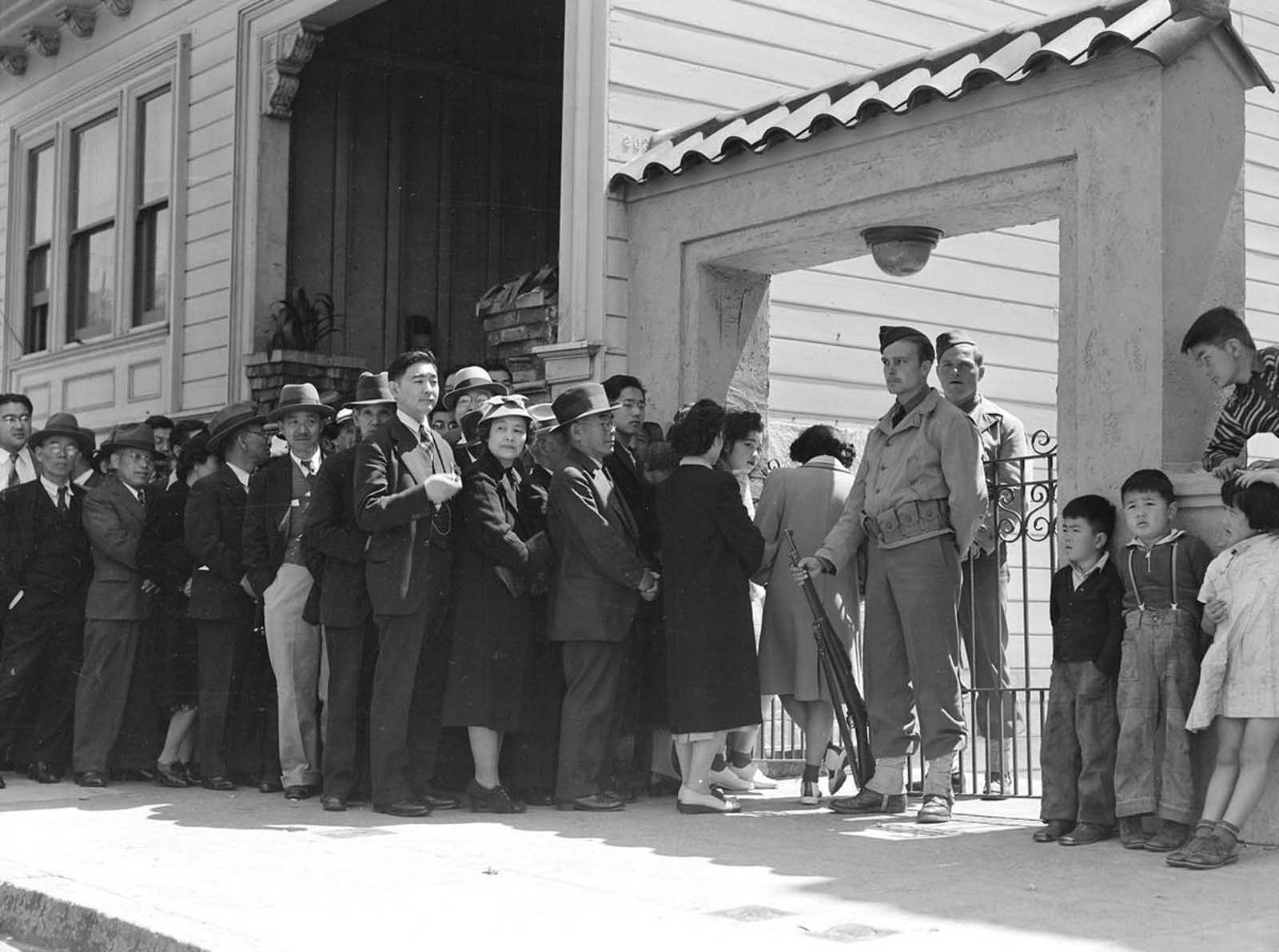 Japanese heads of family and persons living alone form a line outside Civil Control Station located in the Japanese American Citizens League Auditorium in San Francisco, California, to appear for