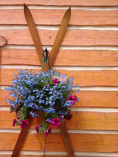 Exterior photo of a large hanging flower basket with purple and pink flowers and an American flag.  Basket hanging over antique skies on  log sided condo.